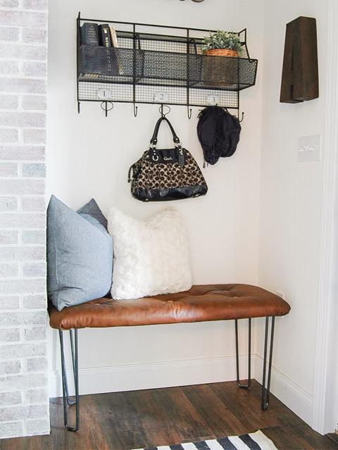 Скамейка и полка с крючками, вместо привычного шкафа в нише, делают эту прихожую более удобной и функциональной