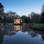 В вечернее время домик с остекленным фасадом выглядит как маяк. (современный,минимализм,архитектура,дизайн,экстерьер,интерьер,дизайн интерьера,мебель,маленький дом,фасад)