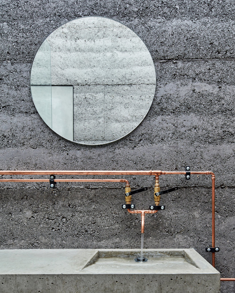 Медные трубы в стиле лофт хорошо смотрятся на фоне бетона в ванной.
