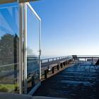 Широкие остекленные окна-двери из главной спальни открывают роскошный вид на океан.