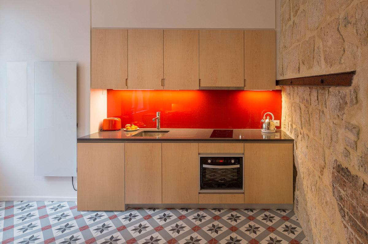 Кухня вдоль одной из стен квартиры. Насыщенный красны придает настроения.