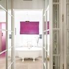 Необычно яркая штора в белой ванной с отдельно стоящей ванной.