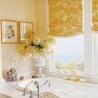 Желтые шторы с интересным принтом на окне с видом на море.