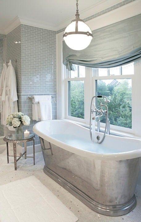Отдельно стоящая ванна у окна с римской шторой.