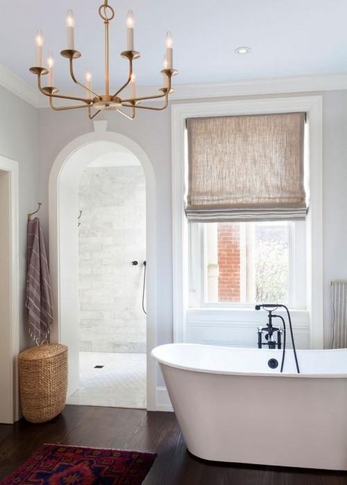 Позолоченная люстра хорошо сочетается с льняной римской шторой.