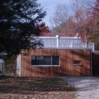 Серое здание студии контрастирует с деревянным фасадом части дома возведенной в 1949-ом году.