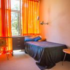 Оранжевые шторы задают настроение спальне.