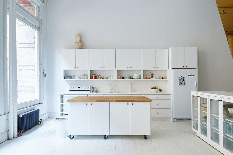 Колеса этого белого кухонного острова с белой столешницей позволяют придвинуть его к кухне, когда нужно готовить, или отодвинуть в сторону, когда нужно больше места.