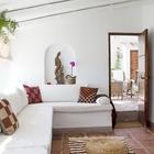 Гостиная внутри дома хорошо освещена благодаря большому окну и белым стенам. Вдоль двух стен расположен диванчик.