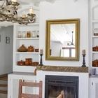 Столовая внутри дома с камином и традиционной встроенной мебелью и полочками. Картину дополняет рустикальная мебель и светильник с подсвечниками. (средиземноморский,средиземноморский интерьер,средиземноморский дом,средиземноморский стиль,архитектура,дизайн,экстерьер,интерьер,дизайн интерьера,мебель,столовая,дизайн столовой,интерьер столовой,мебель для столовой)