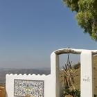 Яркий ковер из керамической плитки на стене ограды является настоящим украшением двора.