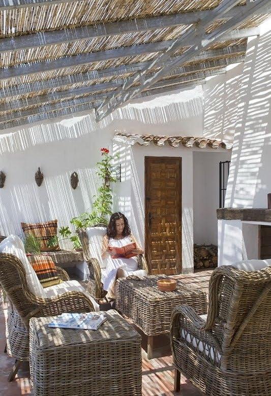 Гостиная с камином на свежем воздухе. Плетеная мебель отлично сочетается с тростниковой крышей.