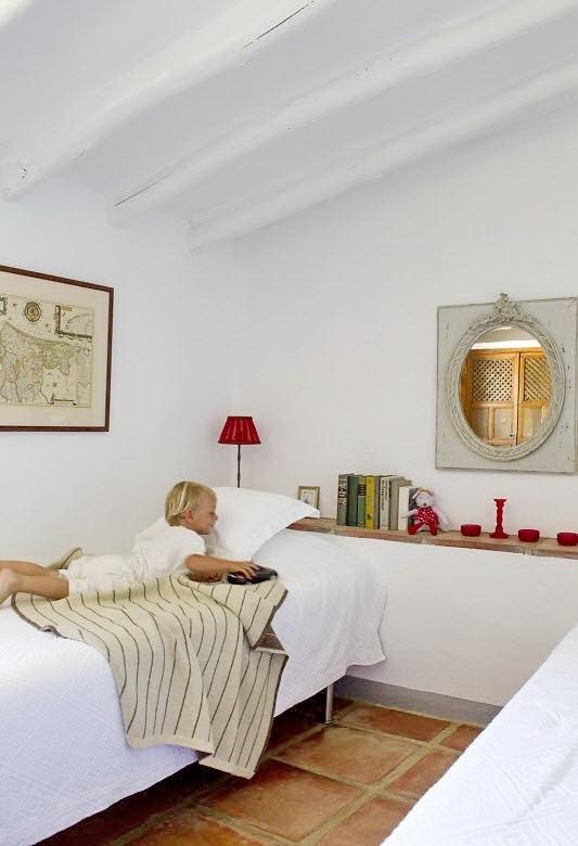 В небольшой детской полка в изголовье кровати заменяет прикроватные тумбочки и полки для книг.