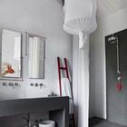 Черный бетонный умывальник. Современная сантехника хорошо вписалась в более традиционный интерьер ванной комнаты.
