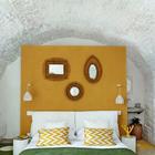 Изголовье кровати в спальне в бывшем винном погребе украшено зеркалами.