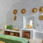 Спальня в вином погребе украшена плетеными элементами, а кирпичные стены просто побелены.