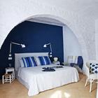 В спальне первого этажа настроение создается успокаивающим синим цветом. Уюта добавляет мебель из ротанга. (средиземноморский,средиземноморский интерьер,средиземноморский дом,средиземноморский стиль,деревенский,сельский,кантри,архитектура,дизайн,экстерьер,интерьер,дизайн интерьера,мебель,спальня,дизайн спальни,интерьер спальни)