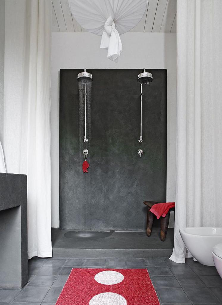 Два душа в ванной комнате. Красные полотенце, коврик и мочалка добавляют красок в черно-белый интерьер ванной комнаты.