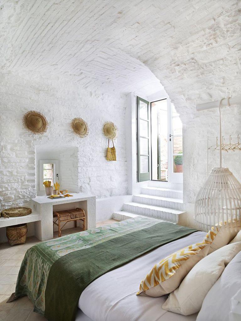 Спальня в цокольном этаже со сводчатыми потолками.