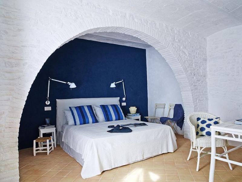В спальне первого этажа настроение создается успокаивающим синим цветом. Уюта добавляет мебель из ротанга.