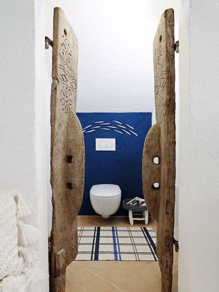 В туалет спальни на первом этаже ведут винтажные резные двери.