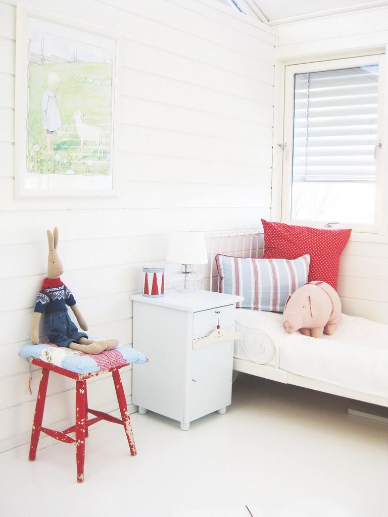 Простой и лаконичный интерьер детской с белым фоном и яркими аксессуарами.