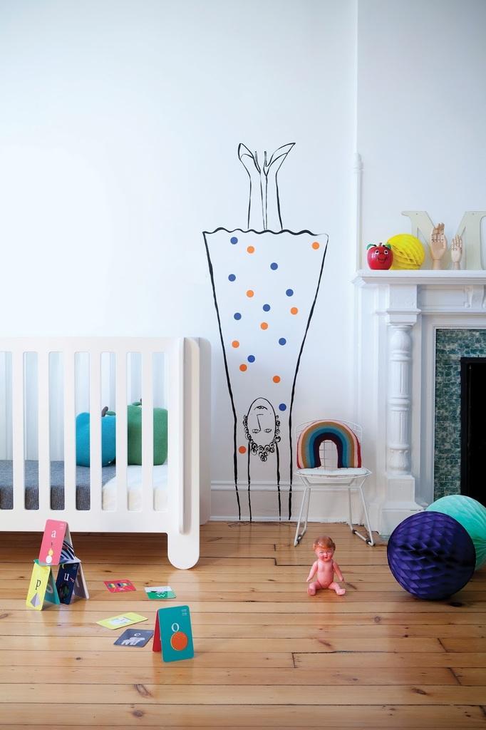 Рисунки на стенах вполне естественны в детской скандинавского стиля, например мама на стоящая на голове