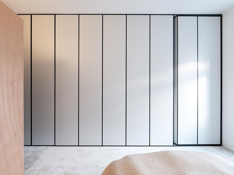 Чистые линии обратной стороны книжного шкафа подчеркивают минимализм спальни.