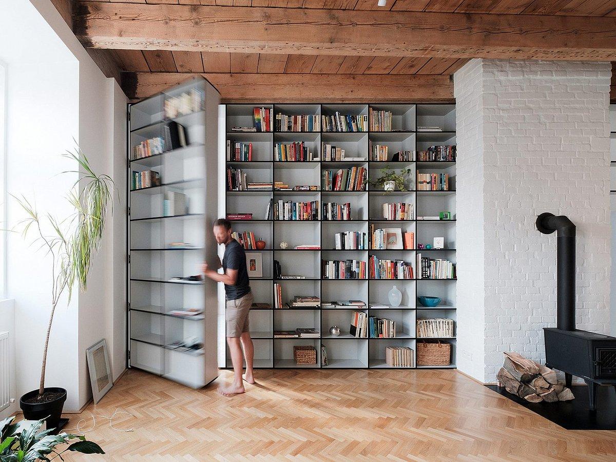 Изюминкой квартиры является открывающаяся секция книжного шкафа в качестве двери в главную спальню.