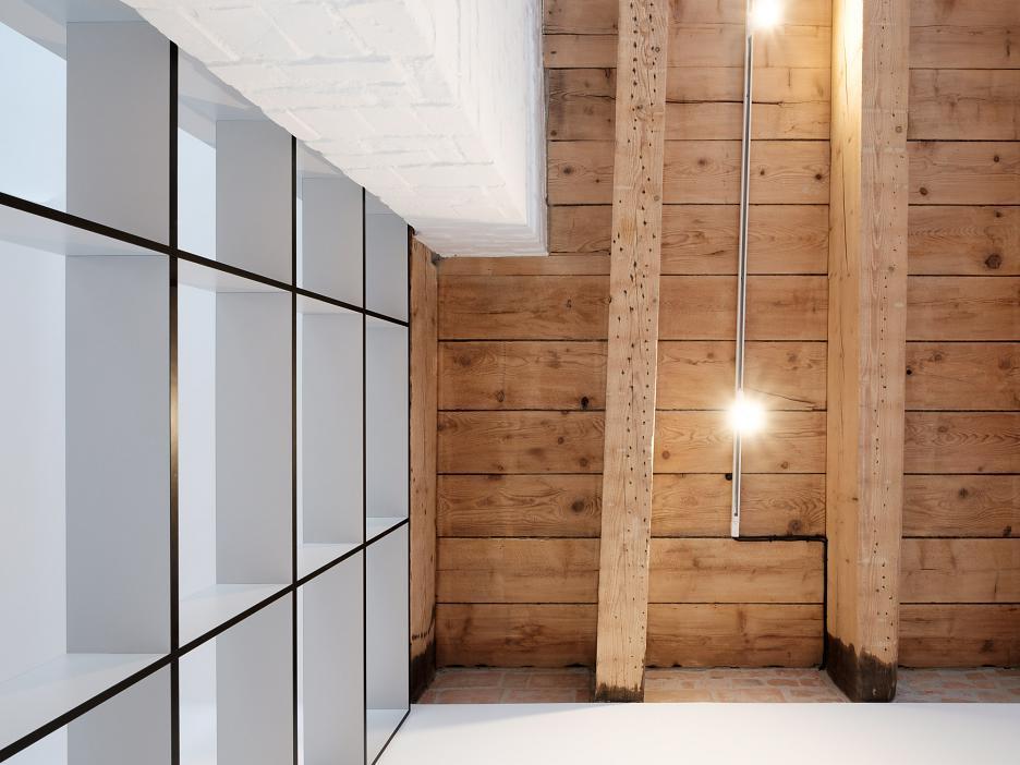 Открытые конструкции потолка, как и книжные полки во всю высоту комнаты визуально увеличивают, и без того немалую, высоту помещения