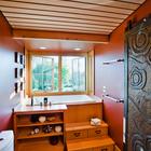 Ванна в ванной комнате на первом этаже установлена у окна в небольшом эркере. Резную дверь вырезали местные мастера.