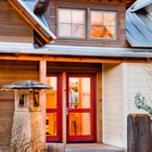 Вход в дом расположен между старой и новой его частями. В дом ведут красные остекленные двери. На крыше видна люкарна над кухней.