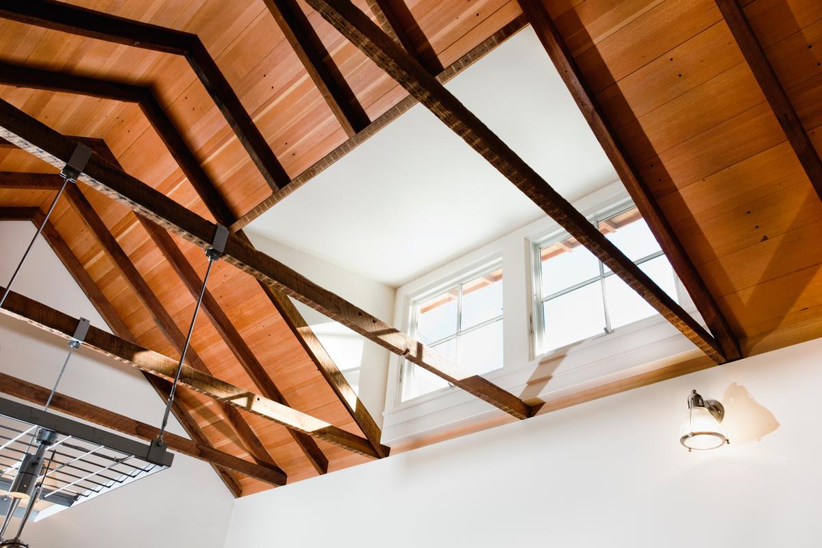 Балки стропильной системы оставлены открытыми, высокие потолки создают ощущения пространства. Окна люкарны с южной стороны ярко освещают кухню.