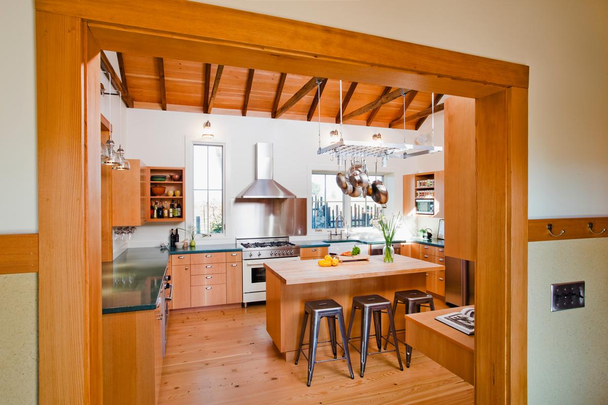 Новая открытая кухня с большой площадью остекления. Окна открывают вид на сад во все стороны и впускает много света. Однако выступы и навесы защищают все окна от высокого летнего солнца