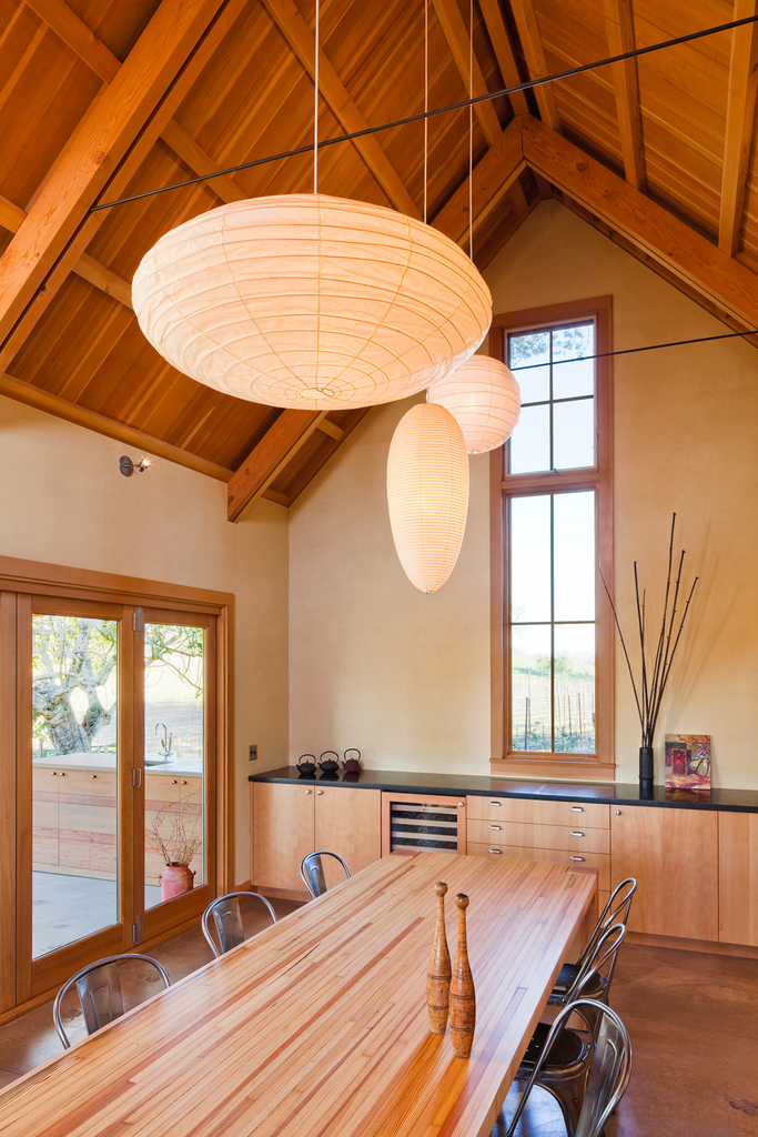 Столовая с глиняными стенами и высокими деревянными потолками стала новым центром дома. Широкая, в 4 метра, складывающаяся остекленная дверь связывает столовую с садом.