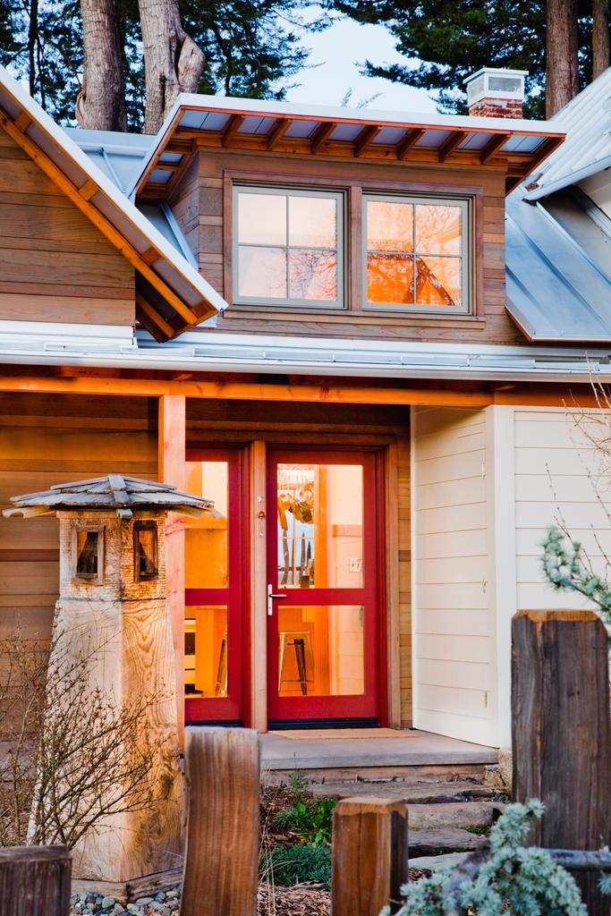 Вход в дом расположен между старой и новой его частями. В дом ведут красные остекленные двери. На крыше видна люкарна над кухней