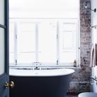 Отдельно стоящая ванна у огромного окна и станы из не оштукатуренного кирпича составляют колоритный интерьер. (индустриальный,лофт,винтаж,стиль лофт,индустриальный стиль,интерьер,дизайн интерьера,мебель,архитектура,дизайн,экстерьер,квартиры,апартаменты,ванна,санузел,душ,туалет,дизайн ванной,интерьер ванной,сантехника,кафель,керамика,фото ванной,идеи ванной)