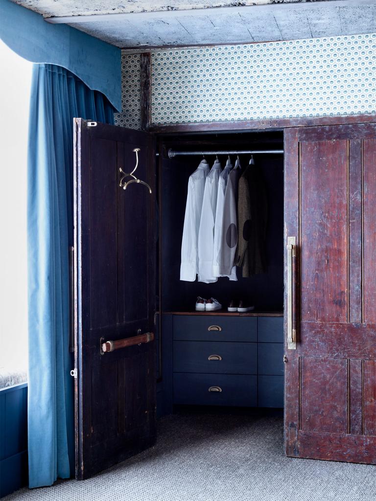 Гардероб в бывшей шахте лифта. Интересны дубовые двери и винтажная вешалка с плечиками на внутренней стороне двери