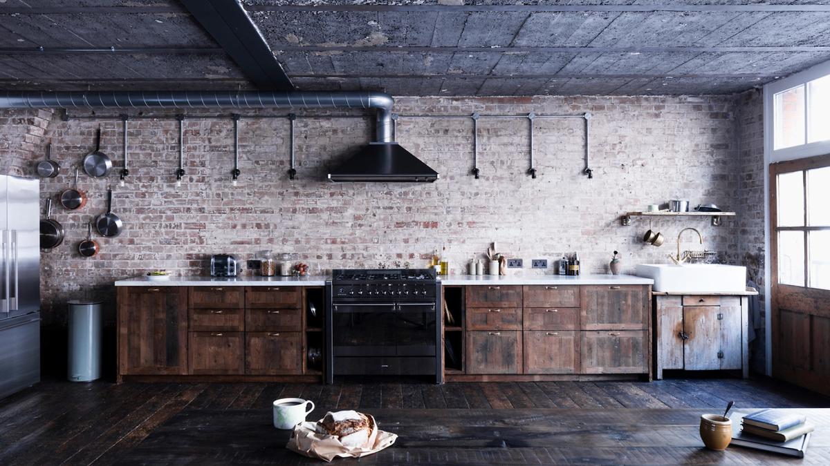На кухне бетон, кирпич и мебель из старой половой доски удивительным образом сочетаются с мраморной столешницей и современной бытовой техникой.