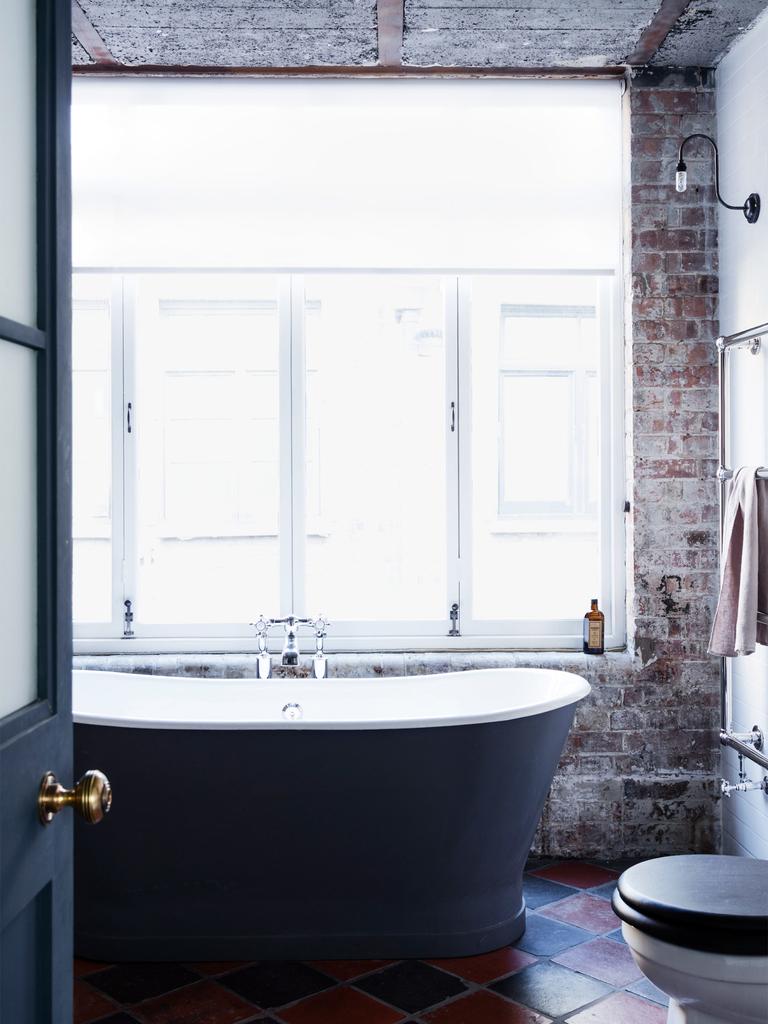 Отдельно стоящая ванна у огромного окна и станы из не оштукатуренного кирпича составляют колоритный интерьер