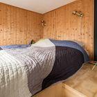 Кровать на антресоли над гардеробом. Стены отделаны лакированной вагонкой, что явно выделяет спальню в гостиной с черными стенами.