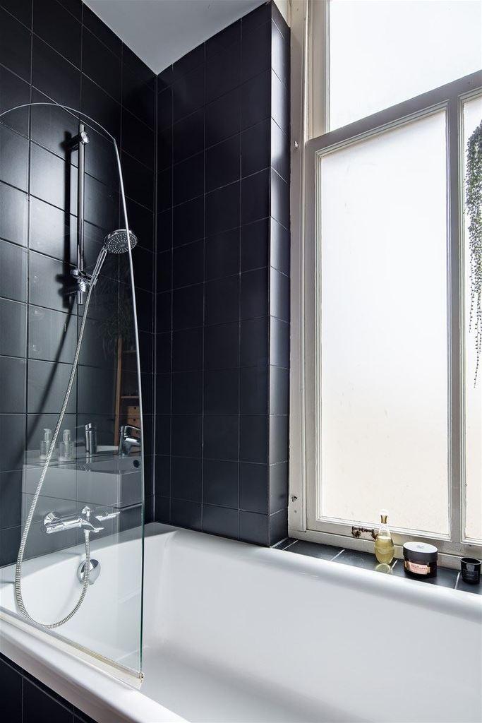 Большое окно в ванной с матовым стеклом ярко освещает комнату и не лишает ее приватности