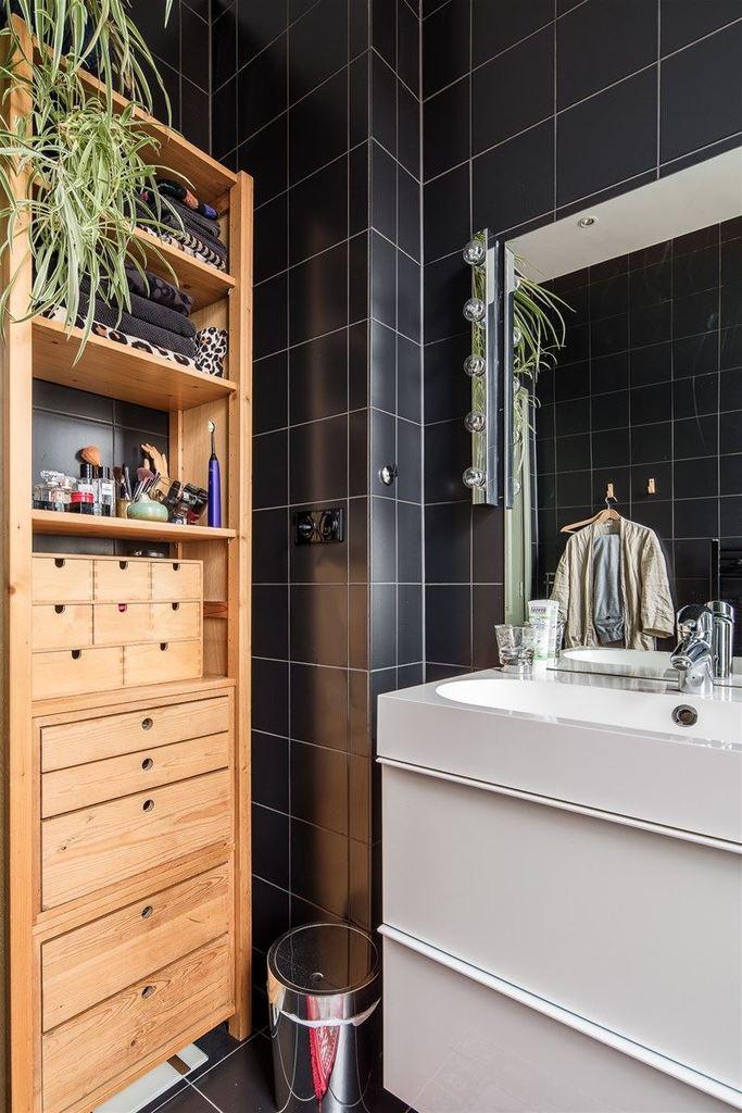Деревянный лакированный пенал замечательно сочетается с черным кафелем стен в ванной.