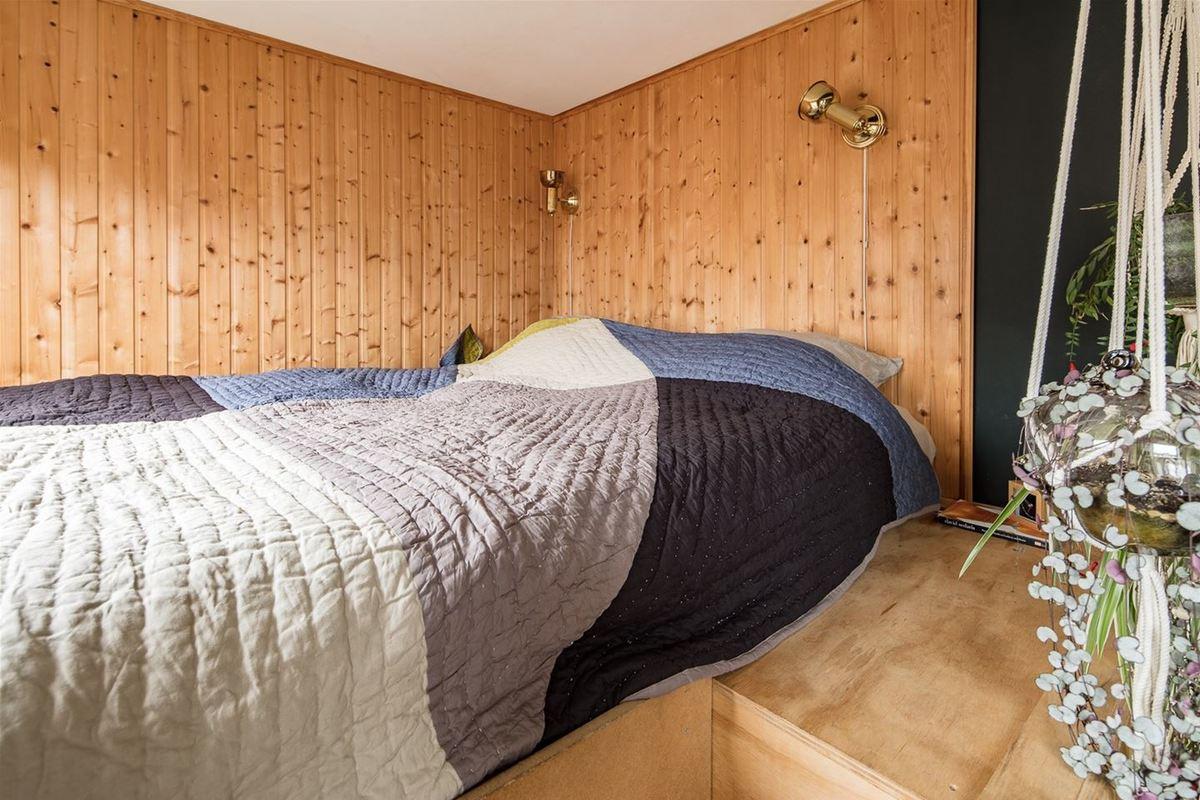 Кровать на антресоли над гардеробом. Стены отделаны лакированной вагонкой, что явно выделяет спальню в гостиной с черными стенами