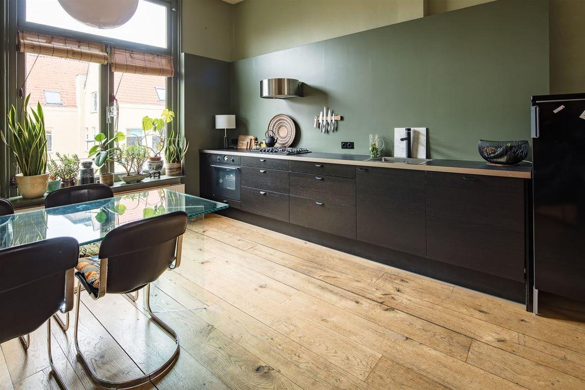 На кухне как и в гостиной можно заметить массу аксессуаров создающих уютную атмосферу - от светильников и подушек на стульях, до рулонных бамбуковых штор, вазонов с цветами на подоконнике и чайничка на плите