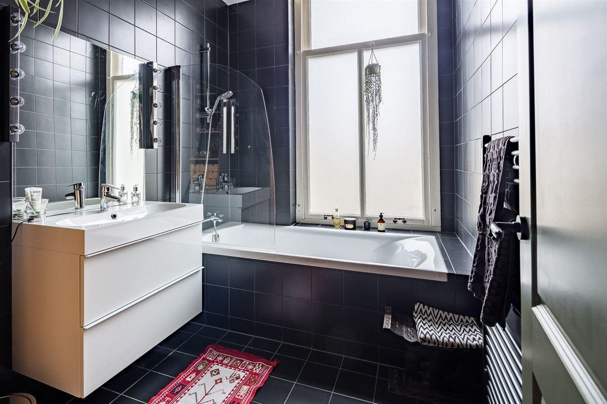 Смело примененный в ванной комнате черный кафель не уменьшает помещение. Яркий коврик добавляет жизнерадостности