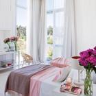 Спальня с высоким угловым окном и выходом на террасу.