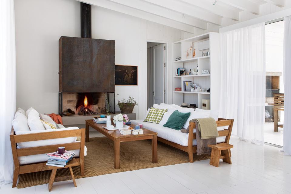 Гостиная со стальным камином и деревянной мебелью с выходом на террасу