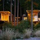Необычный дом сложной формы подсвеченный желтым светом в вечернее время.