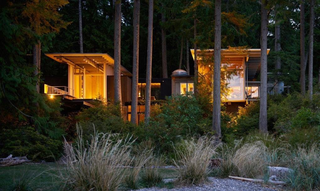 Необычный дом сложной формы подсвеченный желтым светом в вечернее время